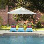 """Bright turquoise towels contrast with the surrounding landscaping…Woodard iron chaises and mosaic iron side tables are from Ken Rash's Arkansas; containers are from Botanica Garden. The pool, designed by Brooks Pool Co., features tile edging and bench seating."""